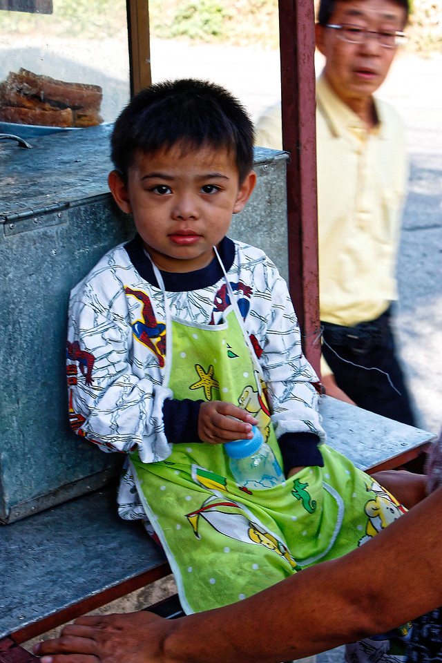 Young lad perched atop his mother's food cart on a street in Chiang Mai