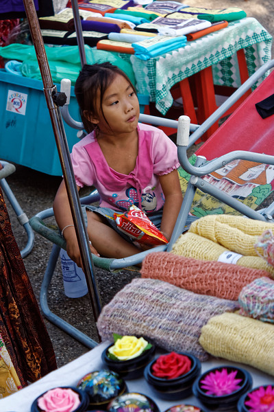 Little girl overseeing her mother's wares at a sidewalk market in Chiang Mai