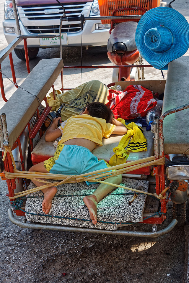 A puzzler: I spotted this little guy, apparently asleep, on a street in downtown Sukhothai, holding what I hope was just a toy gun in his left hand.