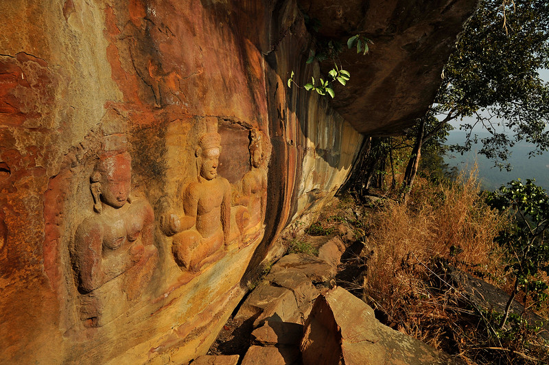 Carved into the face of the cliff at Pha Mo I Daeng, high above the Cambodian border in the extreme southeast corner of Isaan, the three bas-relief figures seen here remain a bit of a mystery, though they are almost certainly Khmer in origin. They are thought to date to the 10th century and the time of Jayavarman IV. Conceivably, the artists responsible for the carvings at nearby Prasat Preah Vihear temple (known as Khao Phra Viharn in Thailand) may have practiced their craft here before beginning work on the temple itself.