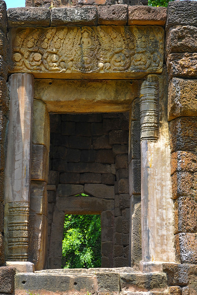 The lintel over the entryway depicts Shiva meditating atop a <i>kala</i> demon, amid botanical motifs—traditional Hindu architectural ornamentation.