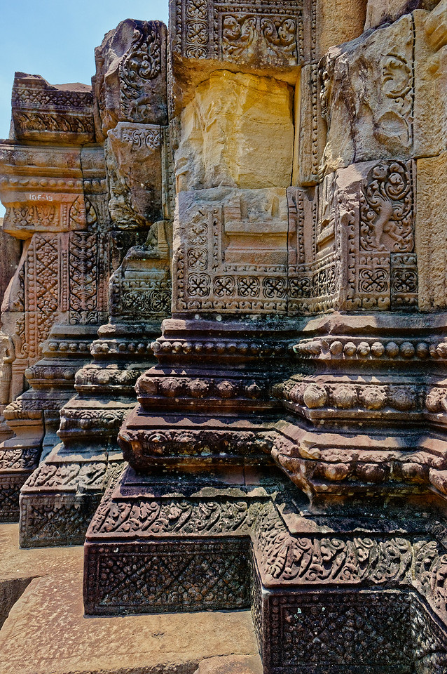 Stylized floral decoration along the base of the main tower. Multiply-redented corners such as this—with vertical 'cuts' made at 90-degree angles—would be incorporated into the design of most later Thai Buddhist temple tower structures known as <i>prang</i> or <i>chedi.</i>