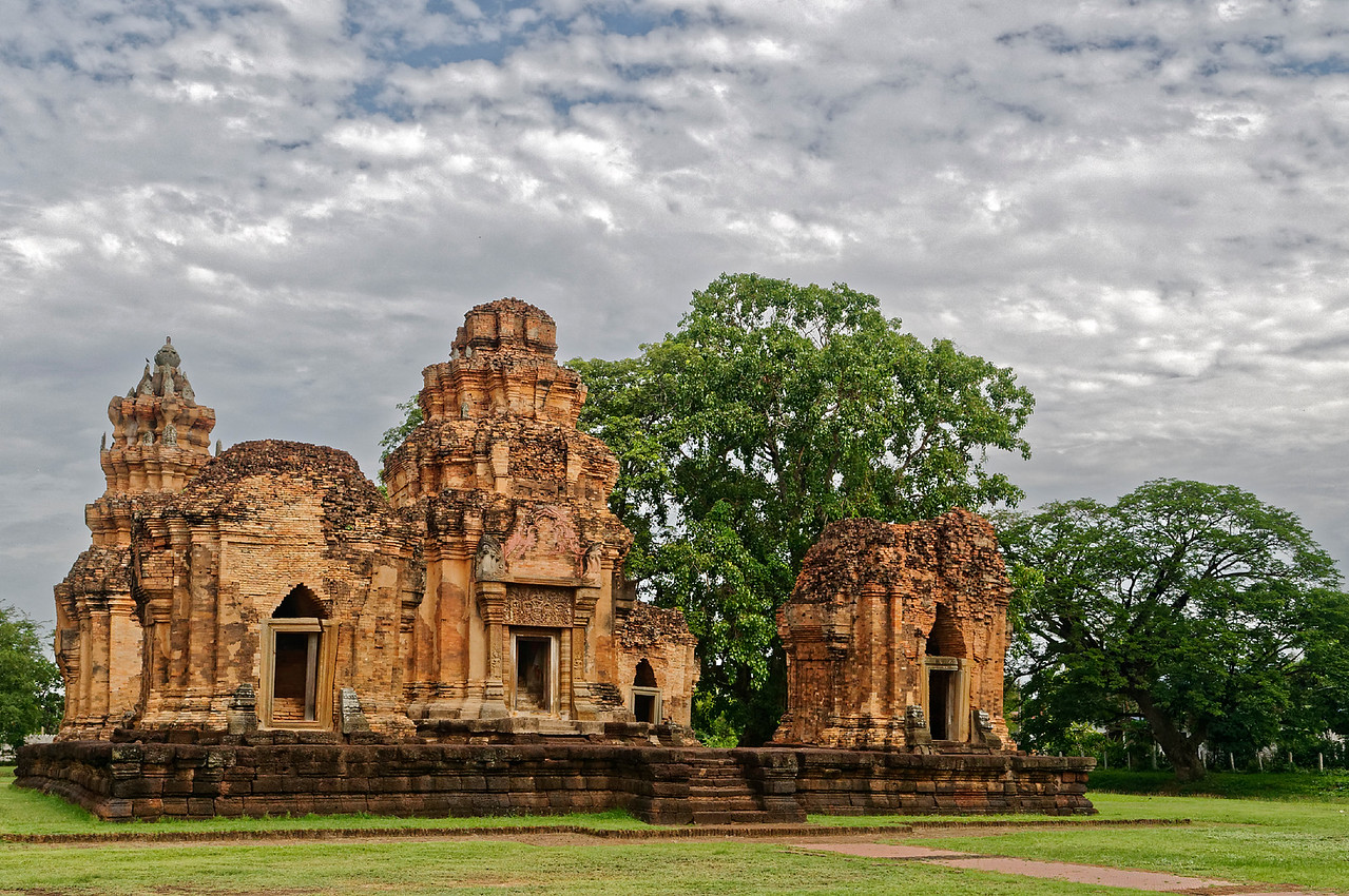 Dating from the 12th century, Prasat Sikhoraphum was built on a raised, rectangular, laterite platform and laid out in the form of a quincunx: one tower at each of the corners and the main tower in the center—a common plan for Khmer sanctuaries in Cambodia but one not found elsewhere in Thailand.
