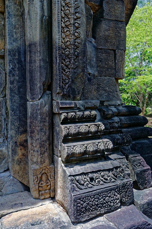 Floral carvings and a meditating yogi or <i>rishi</i> embellish colonettes at the sides of doorways.