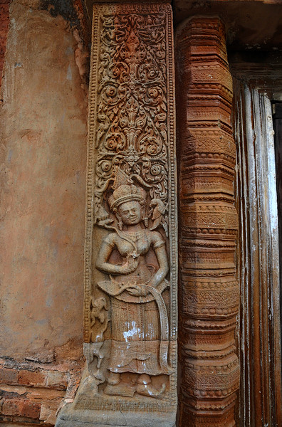 Each <i>apsaras</i> has a parrot by her shoulder and is holding a lotus in her hand. The pose, though somewhat static, suggests movement with the tilt of the head, gentle sway of the hips, and graceful gesturing of the arms and hands.