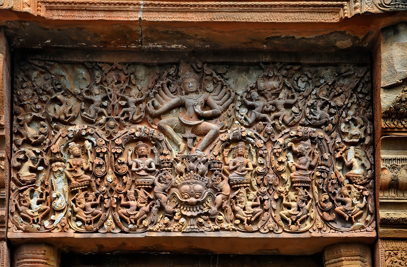 The richly carved lintel over the opening to the sacred space of the central tower features Shiva dancing on a small platform supported by <i>hamsa</i> or geese, who in turn are perched atop the head of a <i>kala</i> demon clasping a <i>singh</i> or lion in each hand. Other deities to the left and right of Shiva's feet are Uma, Vishnu, Brahma, and Ganesh, Shiva's elephant-headed son.