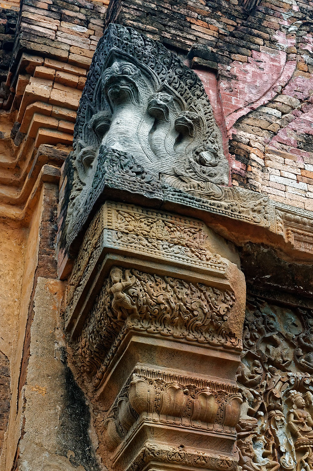 The columns to either side of the doorway are capped by decorative finials featuring a tiny half-bird half-human <i>garuda.</i> Above is a five-headed <i>naga</i> emerging from the mouth of a crocodile-like <i>makara.</i>