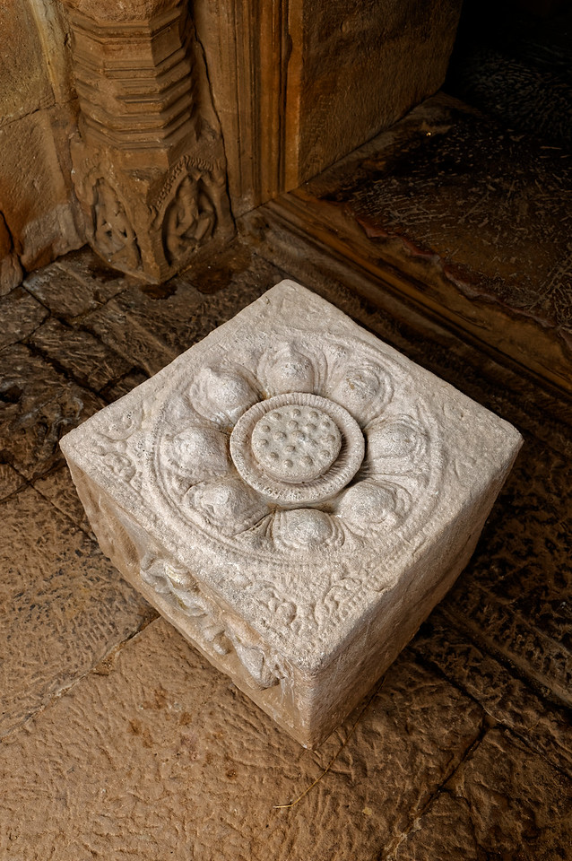At each of the entrances to the <i>mandapa</i> was a carved sandstone block depicting a guardian of a compass direction. The top of this block is carved in a lotus pattern.