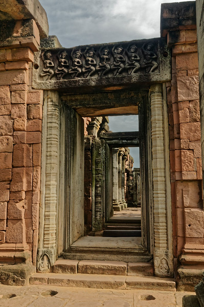 Within the temple grounds, the usual four entry pavilions or <i>gopura</i> were set at the cardinal compass points along an outer gallery. Phimai's principal <i>gopura,</i> providing access through the south wall of the gallery, is seen here. Tantric Buddhist dancers adorn the lintel.