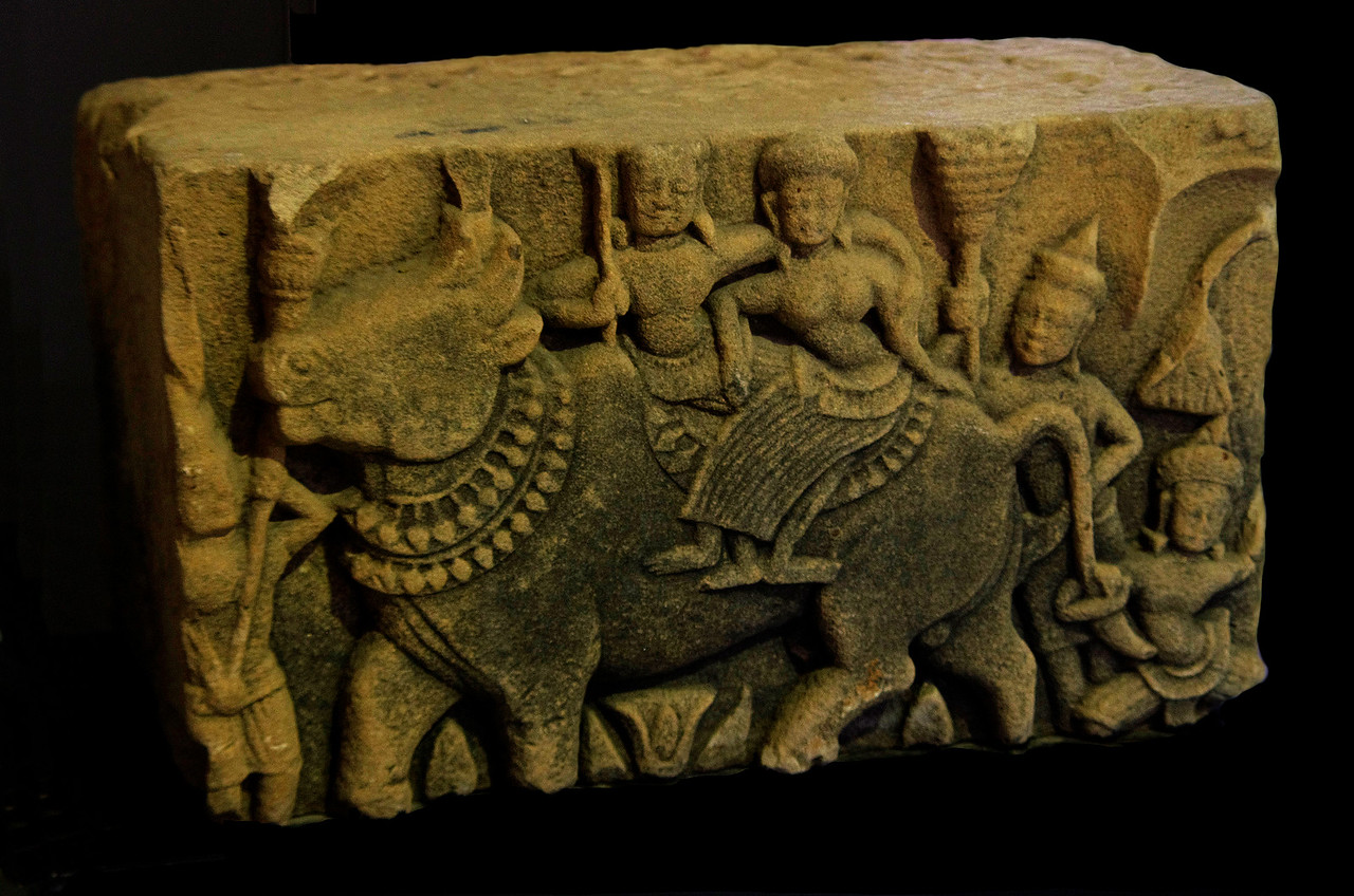 A fragment of a 10th-century pediment found at Prasat Muang Khaek, now at the Phimai National Museum. It depicts Shiva and his consort, Uma, riding atop Shiva's traditional mount, the heavenly bull Nondi, accompanied by attendants.