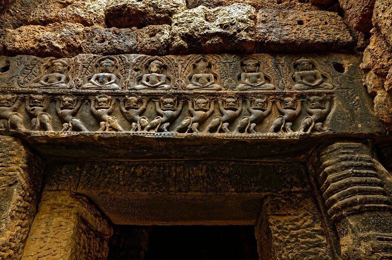 Prang Brahmadat, a laterite tower just to the right as one enters the inner sanctuary from the south, displays more Tantric Buddhist imagery on the lintels above its entrances. Here <i>singh</i> support a platform with meditating Buddhas.