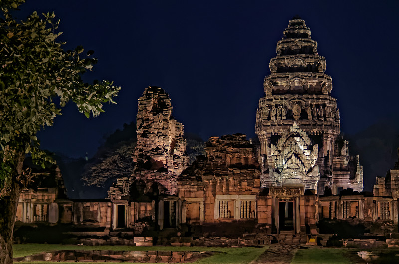 A night view of the temple's inner gallery and the central tower beyond it. The ruins of the tall, red-sandstone structure to the left of the main tower date from the early 13th century.