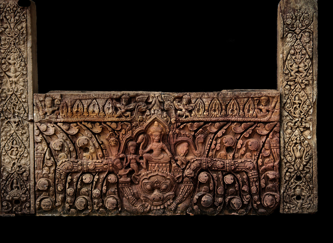 This 11th-century lintel, now in the Phimai National Museum, is from the principal tower at Muang Tham. It depicts the marriage of Shiva and Uma. Shiva is the large figure seated on the <i>kala,</i> with Uma on the left (Shiva's right); both hold lotus buds. On the right is the severely damaged figure of Himavanta, Lord of the Himalayas and father of Uma.