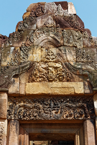 Pediment and lintel above the interior of the eastern entry of the inner <i>gopura.</i> On the pediment, a <i>singha,</i> or lion, preying on an elephant is seen above the <i>kala</i> demon. The lintel shows Krishna doing battle with the <i>naga</i> Kaliya.
