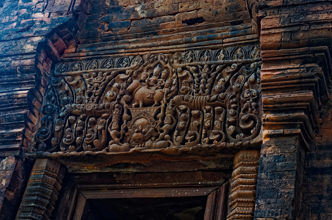 The lintel over the entrance to the north tower in the front row of the inner sanctuary depicts Shiva and Uma on Shiva's traditional mount, the sacred bull Nondi, accompanied by attendants, all on a platform above a <i>kala'</i>s fierce face.