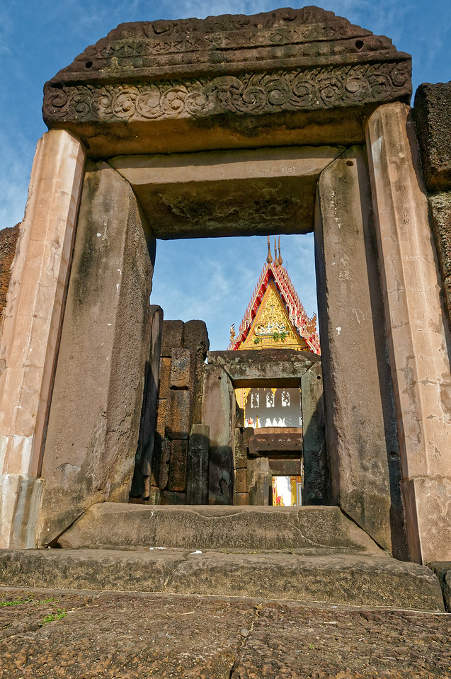 A more recent Buddhist temple has encroached on the grounds surrounding Prasat Sa Kamphaeng Yai. Its assembly hall, viewed from inside the original Khmer sanctuary, provides an incongruous contrast to the early temple's somber laterite and sandstone walls.