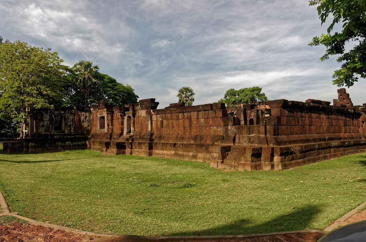 A view of the exterior laterite gallery walls from the northeast. The main <i>gopura,</i> or entrance pavilion, is seen here in deep shade at far left.