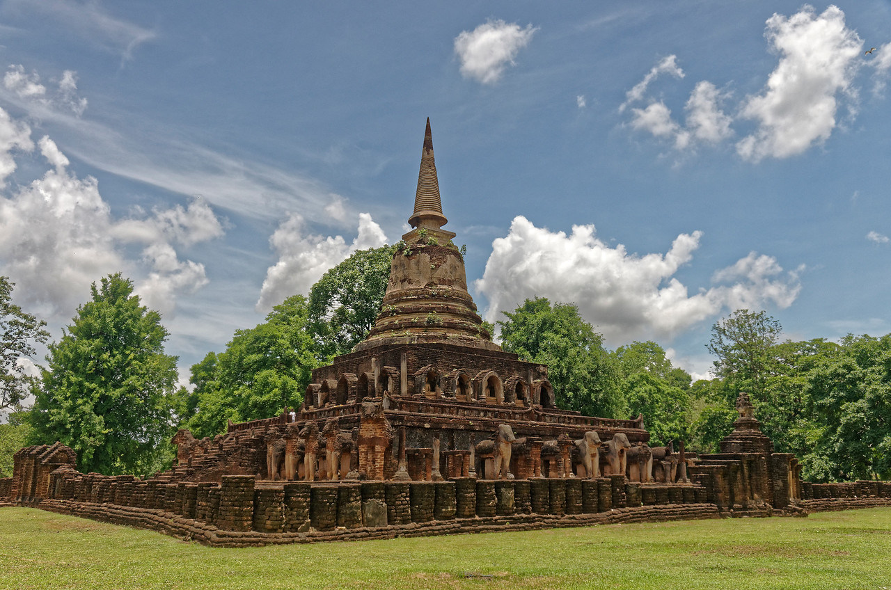 In 1285, with his son ruler of the city, Ramkhamhaeng is said to have built the enormous Sinhalese–style stupa at Si Satchanalai's Wat Chang Lom to house relics of the Buddha. The relic chamber rises above two square supporting tiers, the lower of which was encircled by 36 laterite-and-stucco elephants (the name means 'temple surrounded by elephants'), now in such a state of disintegration as to be unrecognizable as such.