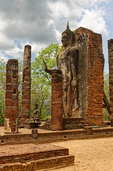 The 41-foot-tall Buddha in <i>abhaya mudra</i> still stands among the ruins of the assembly hall at Wat Saphan Hin. The <i>abaya mudra</i> pose is a gesture of calming or reassurance.