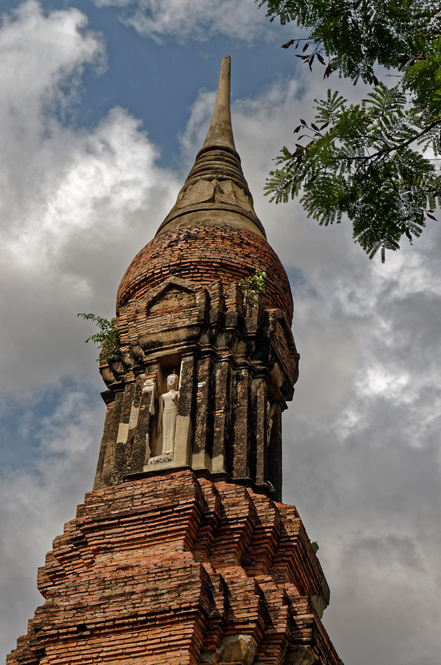 Wat Traphang Ngoen's <i>chedi</i> is unique in design, with four niches at the cardinal points, each containing a standing Buddha image, just below the Sukhothai-style lotus-bud-shaped relic chamber and finial.