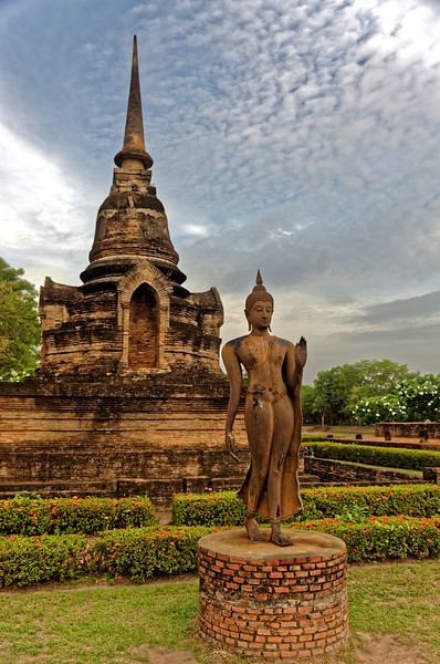 Wat Sa Si's Sukhothai-style Walking Buddha image, with one of its two <i>chedi</i> in the background. The <i>chedi'</i>s four niches would have housed standing Buddhas.