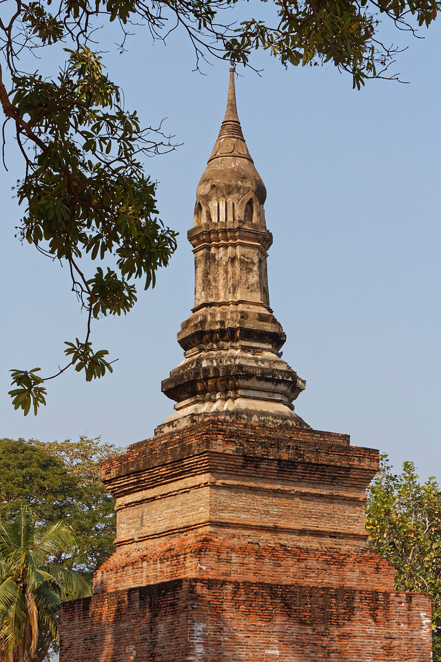 The lotus-bud-shaped relic chamber that sits above the shaft of the central tower and fuses with the tapered finial above it is a distinctive Sukhothai design motif.