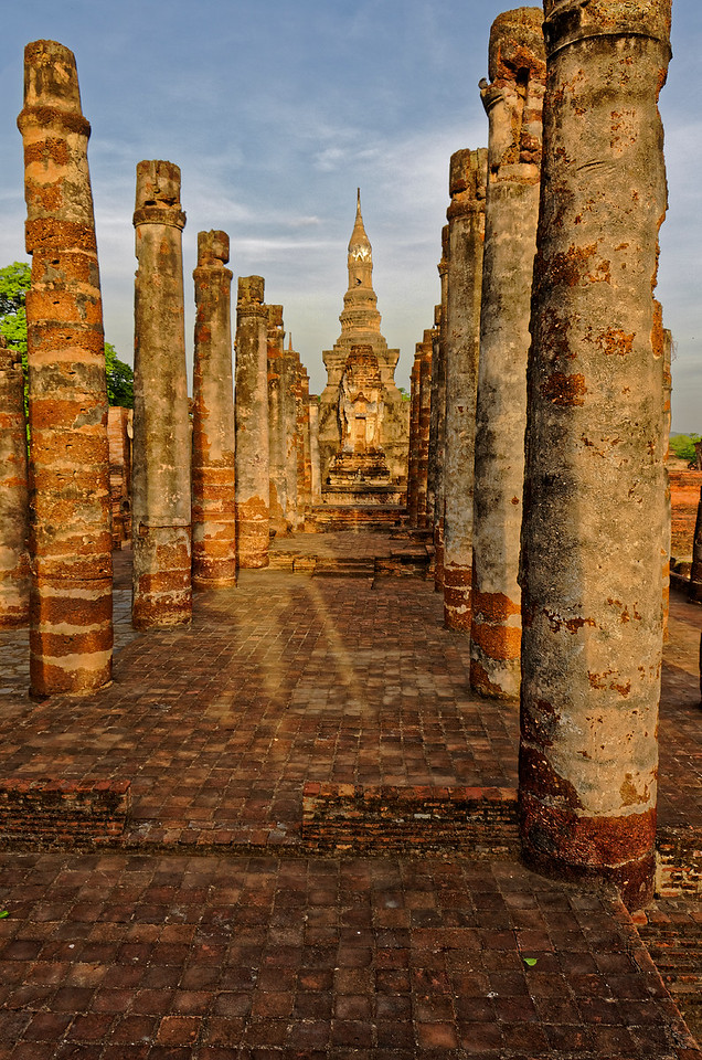The laterite columns and the platforms they stand on are all that remain of Wat Mahathat's two assembly halls. In the background is the temple's central sanctuary.