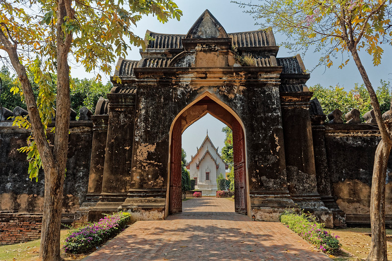 The white, Thai-style structure seen through the entry gateway is the Chanthara Phisan Throne Hall.