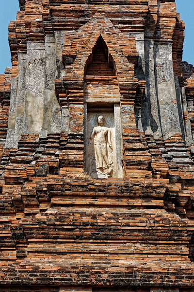 A niche on another tower contains a Sukhothai-derived Walking Buddha.