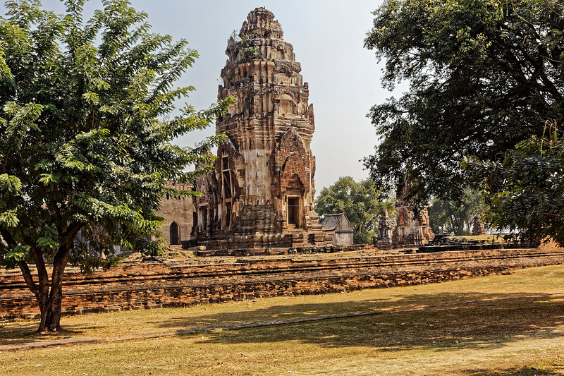 The central tower at Phra Si Rattana Mahathat may be seen to mark a step in the transformation of the traditional Khmer tower to a Thai-style <i>prang.</i> Here at Lop Buri, certain elements from both Phimai and Angkor Wat were further exploited and stressed—such as may be seen in the elongated double pediments above the tower's entrances, for example—to create a greater sense of upward flow to the structure.