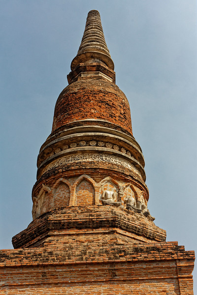 Detail of the Sri-Lankan style stupa seen in the preceding photo, with fragments of meditating Buddhas circling the tower