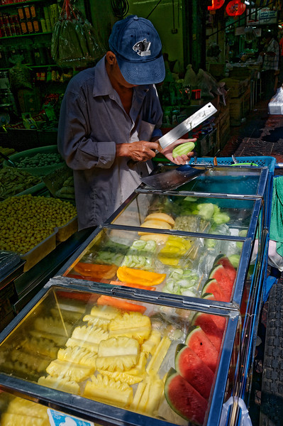 Slicing green mango over a case filled with pineapple, watermelon, cantaloupe, and guava