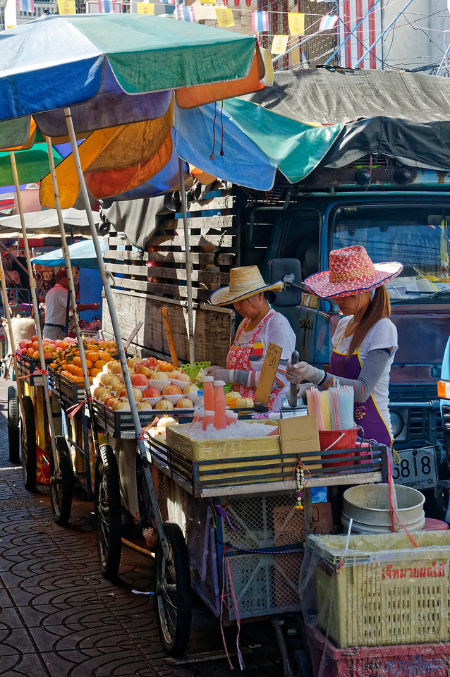 Vendors in Bangkok's Chinatown offering fresh fruit and freshly squeezed juice