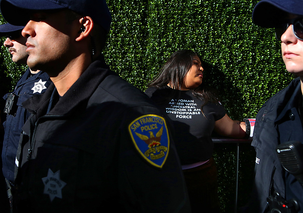 . San Francisco Police officers surround a demonstrator who chained herself to other protesters outside of the Global Action Climate Summit on Thursday.  (Shmuel Thaler -- Santa Cruz Sentinel)