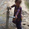 Picture of a young girl using a community hand-pump to fetch water for her home in a semi-urban village