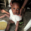 Anne Laterra<br /> Rollins School of Public Health<br /> <br /> Location: Port-au-Prince, Haiti<br /> <br /> This photo is of a young girl, the youngest of nine siblings, living in Port-au-Prince Haiti. We arrived at her mother's house early one morning while she was being fed a breakfast of labouyi or porridge.