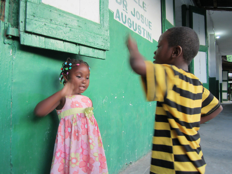 James Lockwood<br /> Emory University School of Medicine<br /> <br /> Location: Hinche, Haiti<br /> <br /> This picture was taken at the L'Hôpital Sainte-Thérèse in Hinche, Haiti.  The two siblings were visiting their family member who had just had surgery by the Emory Project Medishare for Haiti team, on which I was a member as a third year medical student.  The surgical wards were open-air and rat-infested, but these children brought a unique joy to the somber quarters of the hospital.  The children played game after game of a Haitian version of pat-a-cake—laughing, clapping, and dancing as they perfectly executed each move in seamless rhythm.