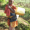 """Five year old girl walking up a hill – getting water from a clean source"""