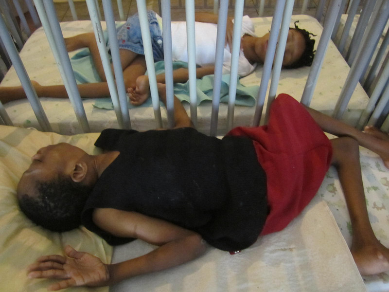 Thuy Trinh<br /> Nell Hodgson Woodruff School of Nursing<br /> <br /> Location: Kingston, Jamaica<br /> <br /> Severely disabled children reach out to each other through the bar crib in a shelter in Kingston, Jamaica.