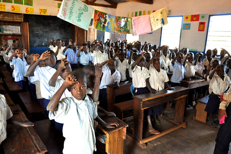 "Cho Hee Shrader<br /> Rollins School of Public Health <br /> <br /> Location: Tanzania<br /> <br /> Students at a Tanzanian school greet adults with a ""Sikimoo!"" a sign of respect. These children are waiting for ITNs which they will take home for their families to use. They are the first generation in a pilot program spanning over two years aimed to distribute Insecticide treated Nets (ITNs) to primary school children. The next year, children in the above grades will receive an ITN to take home. If a household has more than one ITN, it is expected that families will share additional nets with their neighbors. Barriers to ITN use include lack of nets, sleeping outside, and fear that the net will allow mosquitoes through."