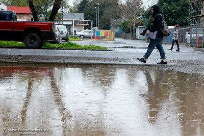 Students walk past a large puddle near W. 5th Street as a little bit of rain falls in Chico, Calif. Tuesday Dec. 13, 2016. More rain is expected Wednesday. (Bill Husa -- Enterprise-Record)