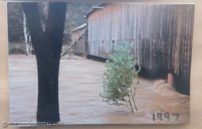 A photo from the flood of 1997 is posted at the Honey Run Covered Bridge as Butte Creek slowly begins to swell below the Honey Run Covered Bridge as a little bit of rain falls in Chico, Calif. Tuesday Dec. 13, 2016. More rain is expected Wednesday. (Bill Husa -- Enterprise-Record)