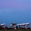 Astronomy telescopes and rising moon at sunset