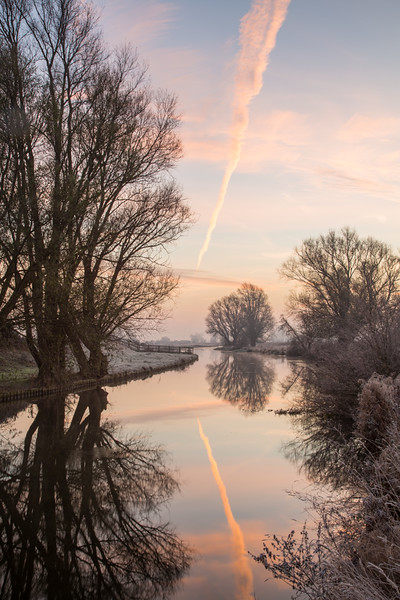 Heading east - vapour trail and reflection at sunrise on River Great Ouse, Flat Bridge, Cambridge