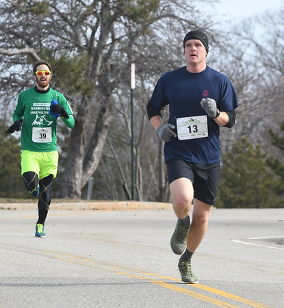 JIM VAIKNORAS/Staff photo Will Briggs edges out Michael Lawless in the 5k race at the Fool's Dual Half Marathon and 5k.