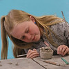 MIKE SPRINGER/Staff photo<br /> Nine-year-old Laila Mears concentrates while shaping clay into a canopic jar, like those used in burial rituals by the ancient Egyptians, during the spring vacation program Tuesday at Cape Ann Art Haven in Gloucester.