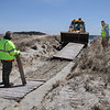 MIKE SPRINGER/Staff photo<br /> Employees of the Gloucester Department of Public Works remove a damaged section of boardwalk Friday at Good Harbor Beach. The section was one of several that were damaged during the winter's nor'easter storms and will have to be repaired or replaced in preparation for the summer beach season.<br /> 4/20/2018