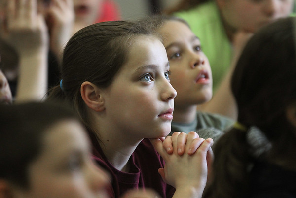 MIKE SPRINGER/Staff photo<br /> Third-grader Malia Bolcome listens Wednesday to the Van Kuijk Quartet at Veterans school. In the background is Malia's classmate Kiara Curcuru.<br /> 4/11/2018