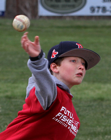 MIKE SPRINGER/Staff photo<br /> Nine-year-old Gabe Anderson throws the ball to first base Tuesday during the Future Fishermen Little League Clinic in Gloucester.<br /> 04/17/2018