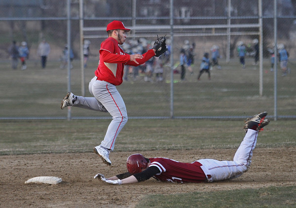 MIKE SPRINGER/Staff photo<br /> Gloucester's Marcus Montagnino slides safely into second base as Everett shortstop jumps to catch the ball during varsity baseball action Wednesday in Gloucester.<br /> 4/11/2018